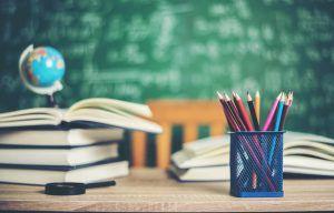 pila de libros, lapiceros y material escolar sobre un escritorio. Detrás se ve una pizarra verde escrita con tiza blanca.