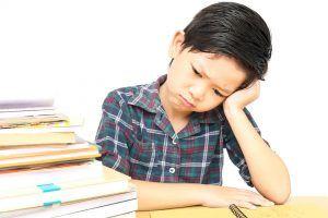 niño con la cara apoyada en la mano, sentado junto a una pila de libros, triste