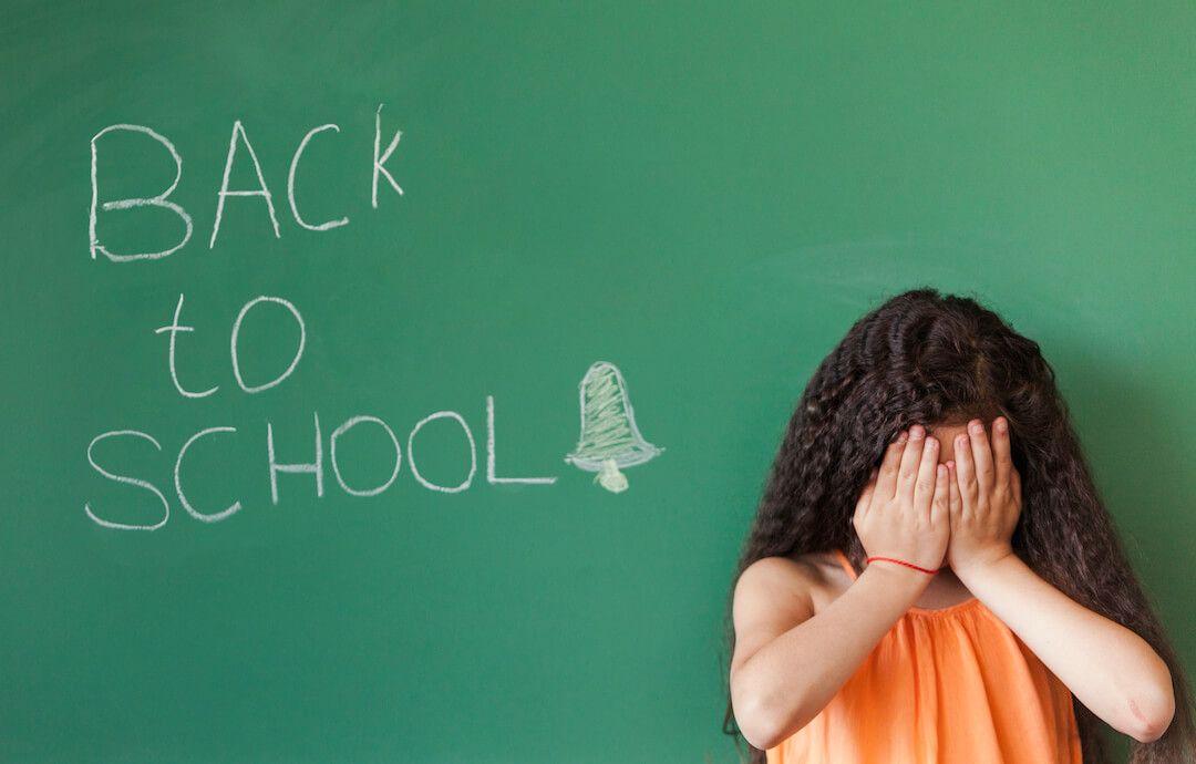 niña tapandose la cara delante de una pizarra que dice back to school
