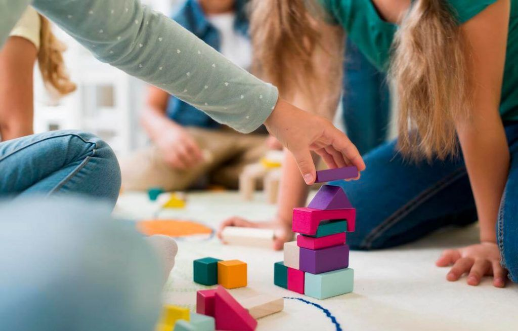 primer plano de manos de niños y niñas sentados en el suelo jugando con bloques de madera