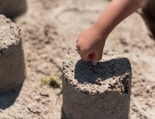mano infantil haciendo un castillo de arena