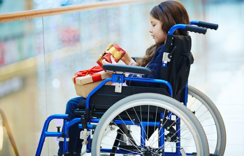 niña en silla de ruedas sosteniendo dos regalos