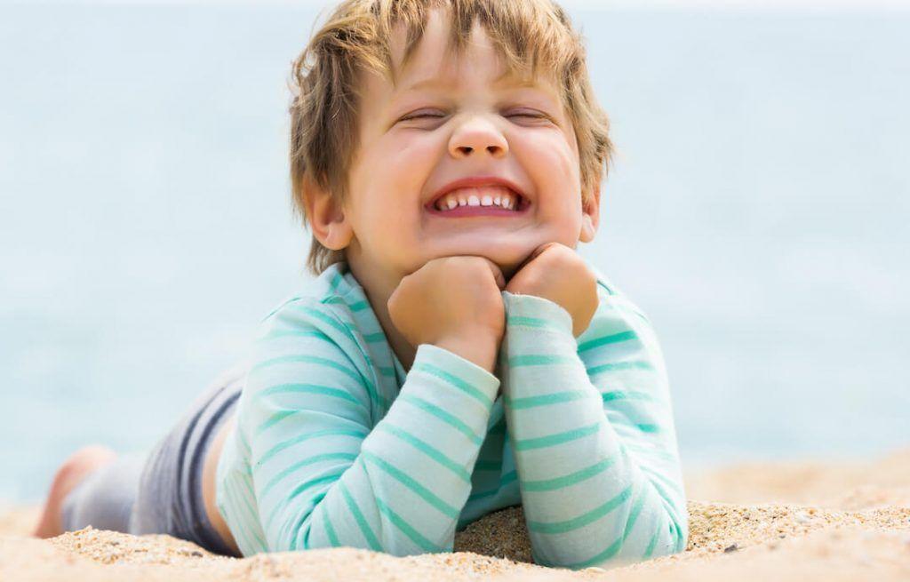 niño sonriendo recostado en la playa sobre la arena, con el mar de fondo