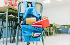 mochila colgada en el respaldo de una silla en una clase de escuela