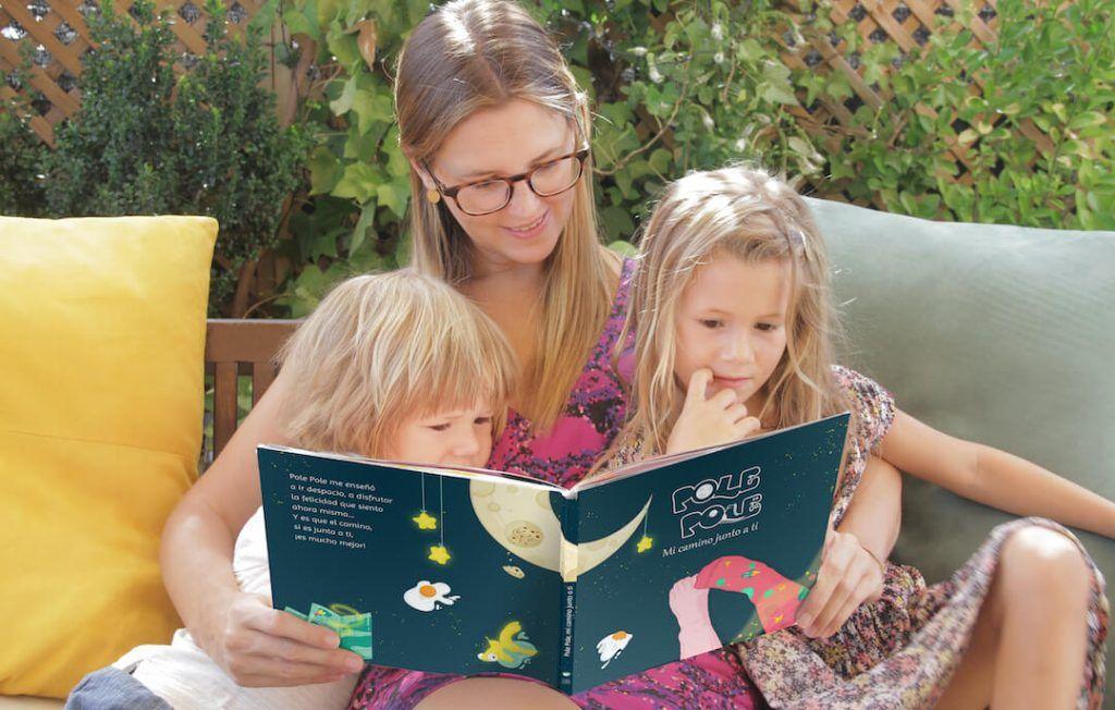 una madre y sus peques sentados mientras leen el cuento Pole Pole. Un gran regalo para el día de la madre.