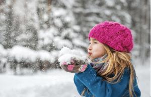 niña rubia con gorro de lana y abrigo, solplando hacia un montón de nieve que tiene en sus manos. De fondo se ve un bosque nevado.