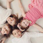 4 niños y niñas recostados en el suelo sonriendo