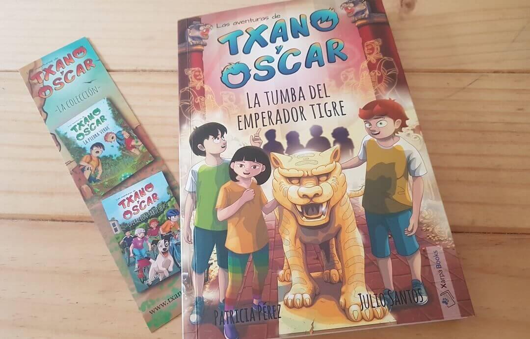 portada del libro de Txano y Oscar La tumba del emperador tigre, donde se ve una ilustracion de los protagonistas junto a su hermana acariciando una estatua de un tigre en la china imperial