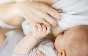 bebé lactando mientras la madres sujeta la camiseta en alto