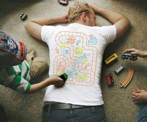 un padre recostado en el suelo boca abajo, con una camiseta que tiene dibujado un circuito para coches. Se ven unos unos niños con coches de juguete jugando sobre este circuito.