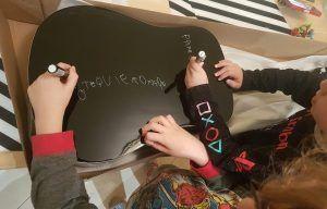 mis hijos con 7 y 5 años, pintando la trasera de una guitarra negra con rotuladores metalizados