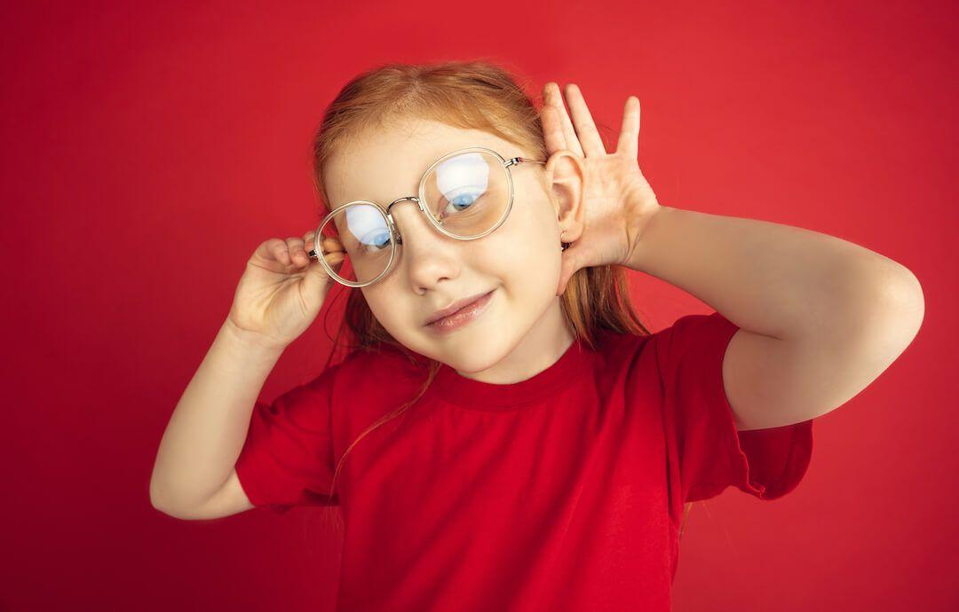 niña pelirroja con gafas con la mano detrás de la oreja haciendo un gesto de oir