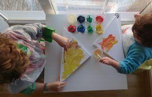 mis hijos con 2 y 4 años pintando unos lienzos triangulares con pintura de dedos