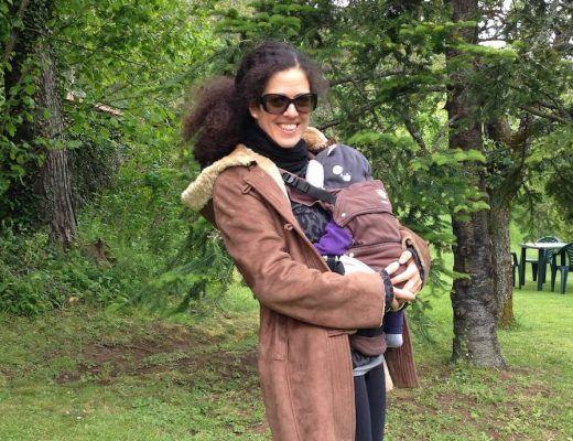 foto en la que se me ve abrigada en un jardín, porteando mi hijo pequeño en una mochila ergonómica Manduca