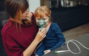 madre colocando un respirador en la cara de una niña sentada en su regazo