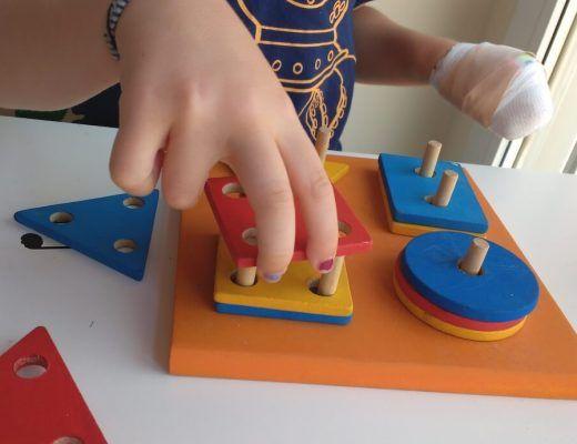 ensartando piezas geométricas de madera con la mano afectada de hemiparesia