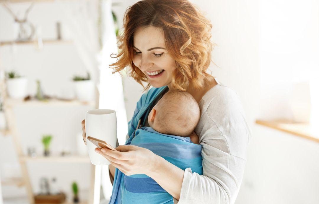madre porteando un bebé mira al movil mientras ríe
