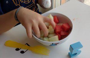 cogiendo fruta en cubos de un bol