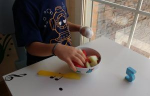 mi hijo comiendo trozos de fruta con la mano afectada por la hemiparesia, mientras lleva la otra vendada en puño