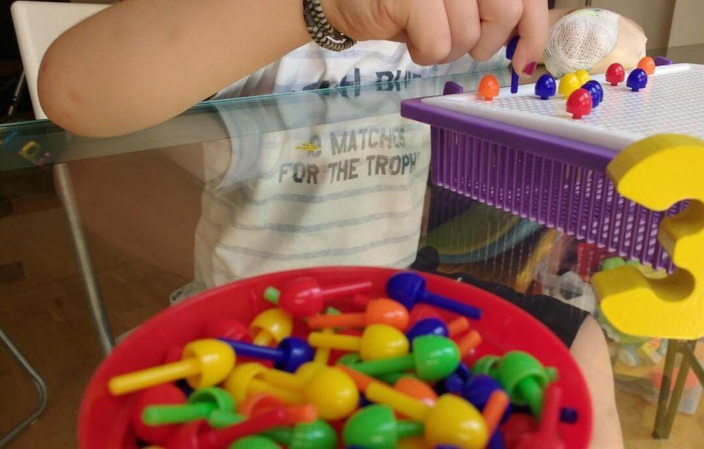 mi hijo con 4 años realizando terapia restrictiva, con una mano vendada y la otra ensartando pinchitos de colores