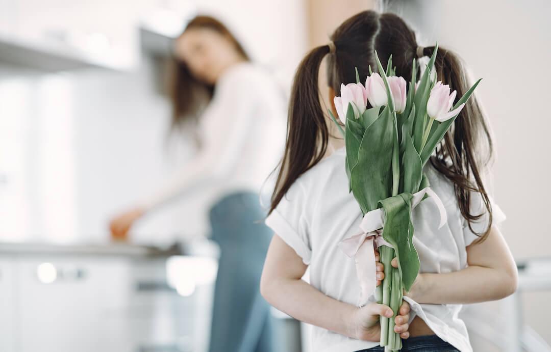 Niña escondiendo un ramo de flores en su espalda, mirando a la madre que está fuera de foco haciendo algo en la mesada de la cocina.