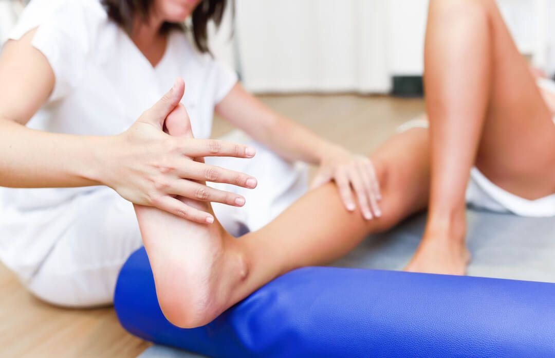 Fisioterapeuta haciendo estiramientos a un paciente recostado en una camilla