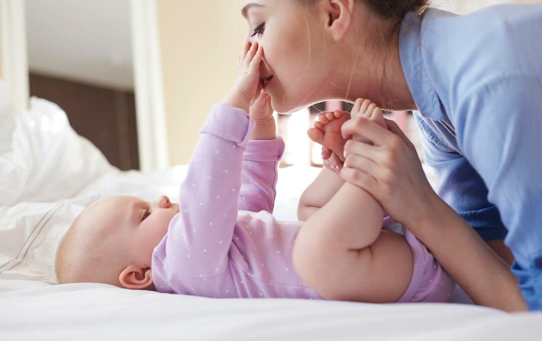 mujer cogiendo los pies de un bebé recostado que la mira y le toca la cara con sus manitas
