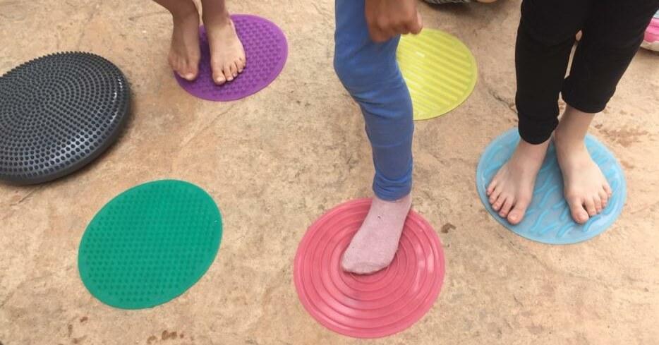varios peques de pie en las alfombrillas sensoriales circulares de silicona de colores, algunos descalzos y otros en calcetines