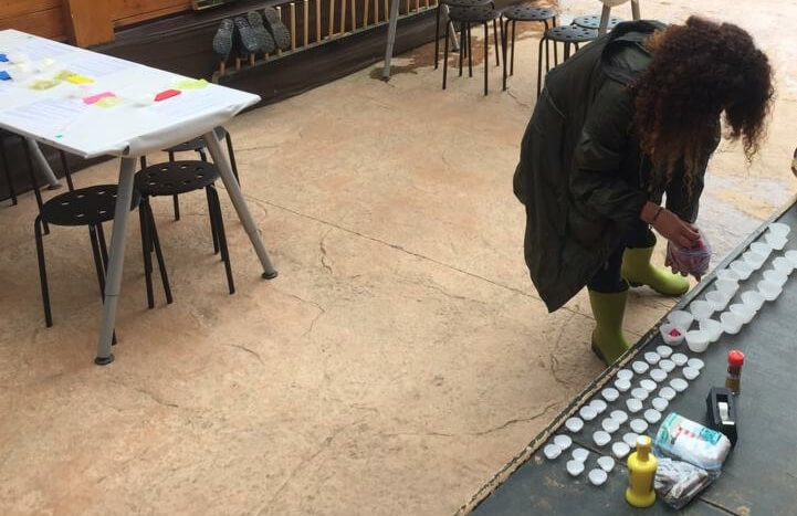 foto en la que se me ve agachada, preparando los materiales para el circuito sensorial sobre una rampa. Detrás se ven dos mesas con bancos, sobre ellas están parte de los materiales