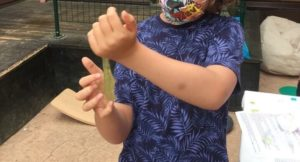 mi hijo de 9 años, de pie, pasando un slime amarillo de una mano a otra
