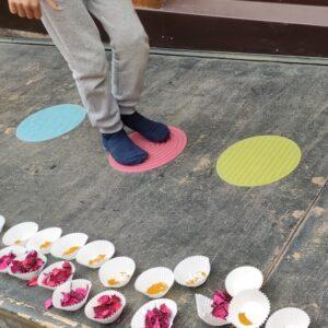 niño caminando sobre alfombrillas sensoriales de silicona de colores circulares. A su lado hay moldes de papel de madalenas rellenos de curry o popurri de rosas