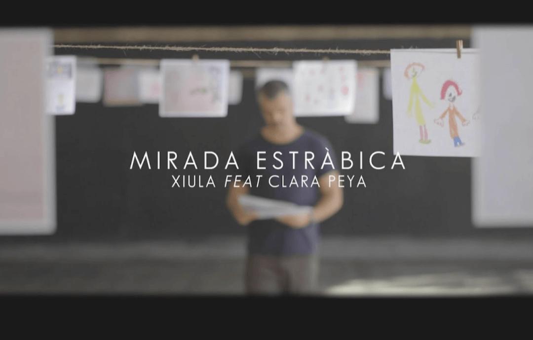 fotograma del videoclip de Xiula, donde dice MIRADA ESTRABICA y se ve al cantando con un dibujo en la mano y detrás varias cuerdas donde cuelgan dibujos en folios blancos